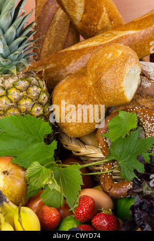 Fruits and bakery like pineapple, strawberries, vine, bread, rolls and white bread arranged in a group, natural - Stock Photo