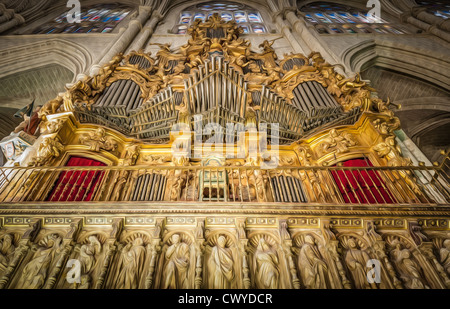 Massive wall with stained glass windows and arches. Huge pipe organ place in gold colours. Sculptures of saints - Stock Photo