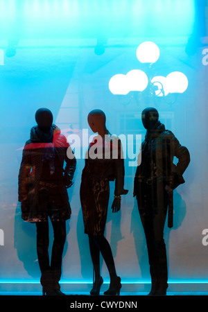 Night view of the french shop window with the street reflection in it and mannequins inside the shop showcasing - Stock Photo