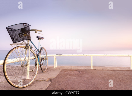 Old and vintage bicycle at the railing near the sea. Blue sea and sunset sky in background. A lot of copy space. - Stock Photo