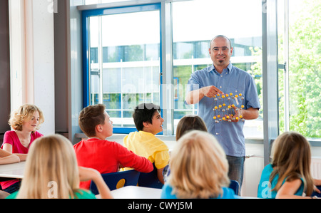 Teacher with molecular model in class - Stock Photo