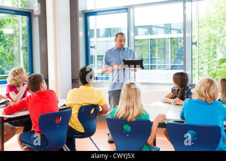 Teacher explaining solar panel in class - Stock Photo