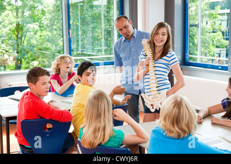 Schoolgirl holding spinal column model in class - Stock Photo