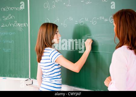 Schoolgirl writing formula at blackboard - Stock Photo