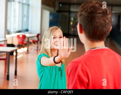 Teenage girl reaching out her hand to teenage boy - Stock Photo