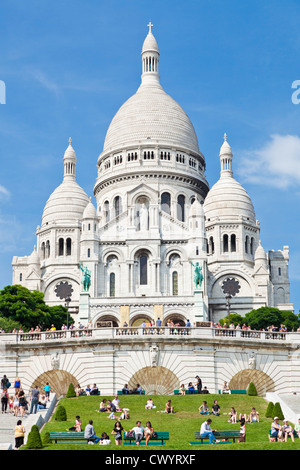 Crowds sat on the grass below Sacre Coeur in the Square Louise Michel Paris France EU Europe - Stock Photo