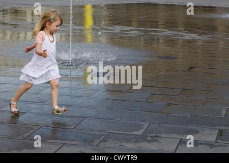 young girl 5 6 7 8 runs running street fountain - Stock Photo