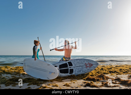Couple with stand up paddle boards, Tarifa, Cadiz, Andalusia, Spain. - Stock Photo