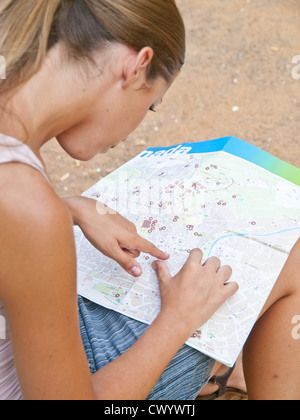 Young woman reading city map - Stock Photo