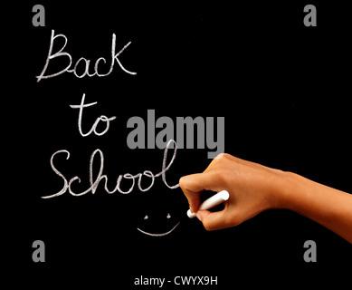 Handwriting phrase 'back to school' on blackboard in classroom, conceptual image of school time, teacher arm holding - Stock Photo