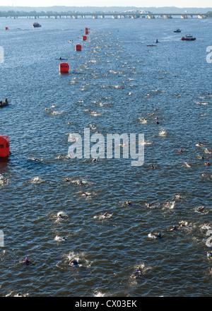 Triathlon swimmers racing in river - Stock Photo