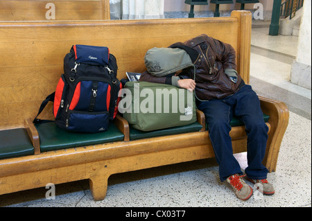 Sleeping male traveler taling a nap on a wooden bench, Pacific Central Railway Station, Vancouver, British Columbia, - Stock Photo