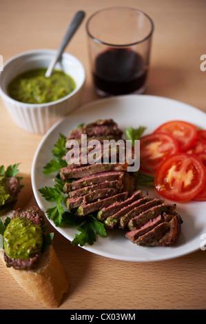 Sliced steak with chimichurri sauce. - Stock Photo