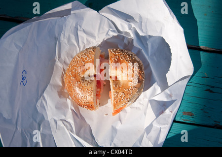A sesame seed bagel with lox (smoked salmon), cream cheese, onion and tomato, sitting on a paper wrapper, from Spring - Stock Photo