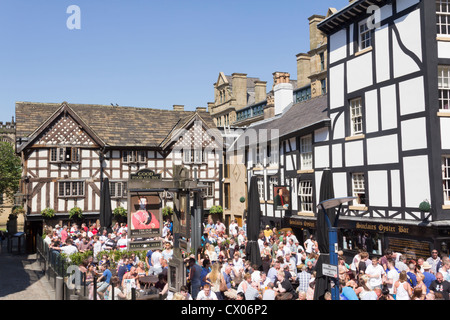Busy crowd of customers in the beer gardens of the Old Wellington and Sinclairs Oyster Bar, Shambles Square, Manchester. - Stock Photo