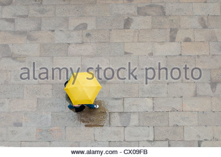 Two people shelter under an umbrella in Venice. - Stock Photo