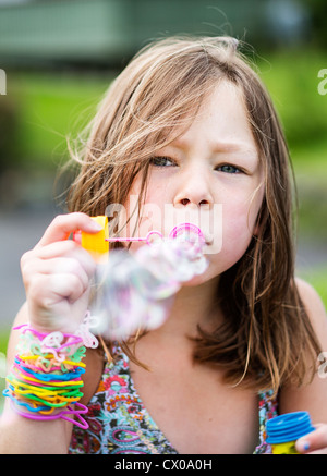 Little girl blowing soap bubbles in the summer wearing colorful arm rings - Stock Photo