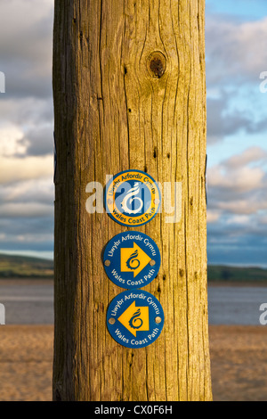 Waymarker signs for the Wales Coast Path on Aberdyfi (Aberdovey) beach (in evening light) Dyfi estuary, Gwynedd, - Stock Photo