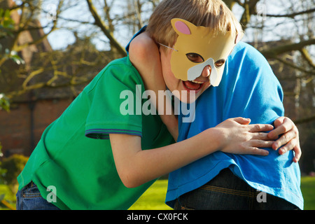 Boy Wearing Cat Mask Fighting with Friend - Stock Photo