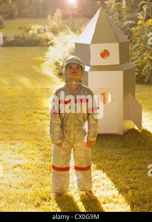 Boy Wearing Space Suit Standing in front of Cardboard Rocket Spacecraft - Stock Photo
