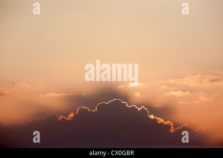 Silver lining as the sun disappears behind a line of clouds - Stock Photo
