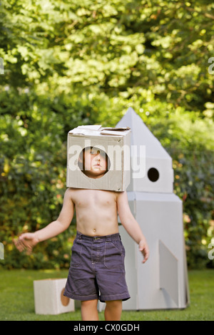 Boy Wearing Homemade Cardboard Helmet Playing in front of Rocket Spacecraft - Stock Photo