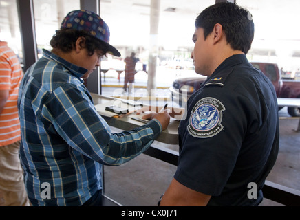 Mexican citizens wait  fill out paperwork to travel to the US. Security measures include fingerprinting by US Border - Stock Photo