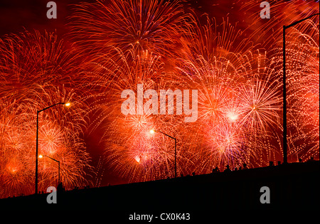 FPeople watch Fourth of July Fireworks from elevated overpass. - Stock Photo