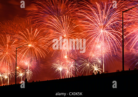 People watch Fourth of July Fireworks from elevated overpass. - Stock Photo
