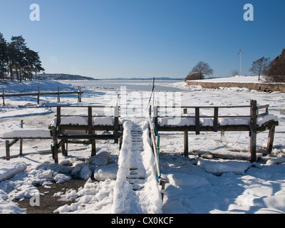 Snow covered pier at Bygdøy in Oslo Norway with view of the ice covered Oslofjord - Stock Photo