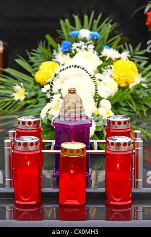 Illuminated votive candles glows on a grave, lantern - Stock Photo