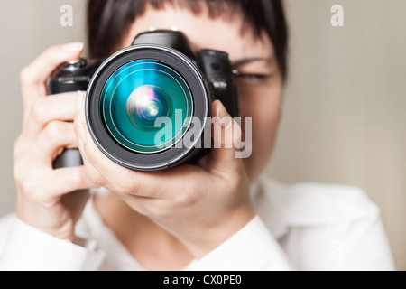 Pretty woman is a professional photographer with dslr camera - Stock Photo
