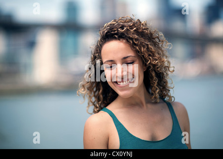 Portrait of woman with curly hair, smiling - Stock Photo