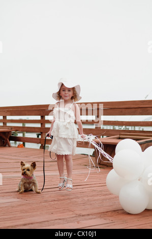 Girl with dog holding bunch of white balloons - Stock Photo