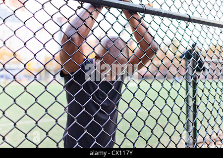 Man behind a chain link fence - Stock Photo
