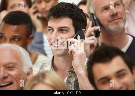 Man on cell phone with group of people - Stock Photo
