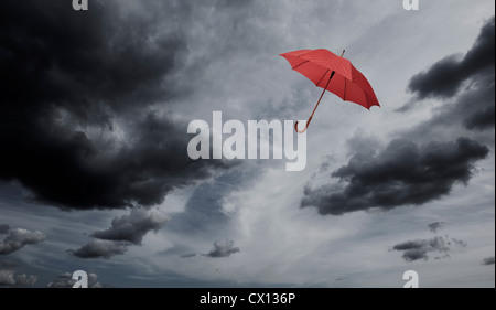 Red umbrella floating through cloudy sky - Stock Photo
