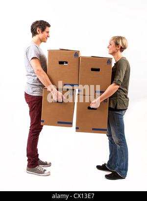 Symbolfoto Umzug, Auszug, umziehen. Junges Paar trägt Umzugskartons. Umzugskisten aus Pappkarton.