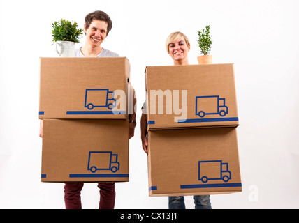 Symbolfoto Umzug, Auszug, umziehen. Junges Paar trägt Umzugskartons und Zimmerpflanze. Umzugskisten aus Pappkarton.