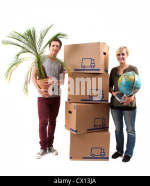Symbolfoto Umzug, Auszug, umziehen. Junges Paar mit Umzugskartons Globus und Zimmerpflanze. Umzugskisten aus Pappkarton.