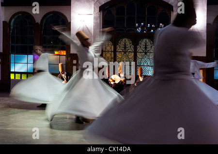 Whirling dervishes perform to visitors in the event hall of Sirkeci Train Station on October 21, 2005 in Istanbul, - Stock Photo