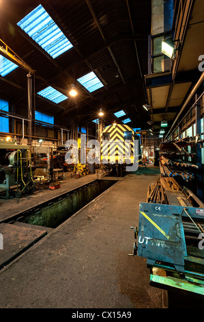 A Diesel shunter undergoing maintenance in the engine sheds at Grosmont on the North Yorkshire Moors Railway - Stock Photo