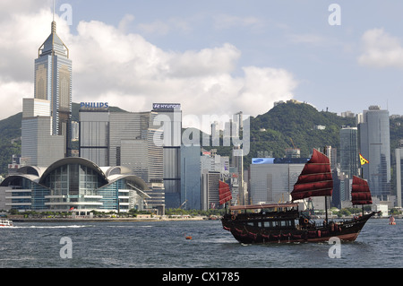 Chinese junk boat with the skyline of Hong Kong in the background (Hong Kong, China) - Stock Photo
