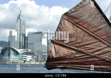 Chinese junk boat sail with the skyline of Hong Kong in the background (Hong Kong, China) - Stock Photo