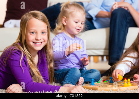 Family playing board game ludo at home on the floor - Stock Photo