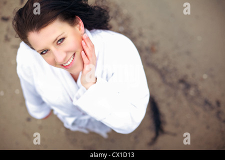 Woman in bathrobe looking fresh and clean and smiling for the camera in high angle shot - Stock Photo