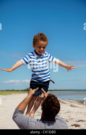 Dad lifting his young son against the bright summer sky - Stock Photo