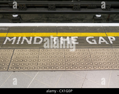Mind the gap London underground railway sign on the edge of the platform. - Stock Photo