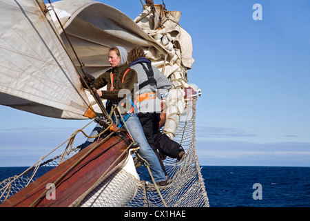 Sailors handling sails on bowsprit of the tall ship / barquentine Antigua sailing with tourists towards Svalbard, - Stock Photo