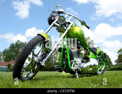 Seen from below a custom painted chopper motorcycle on grass and with chrome finished engine - Stock Photo